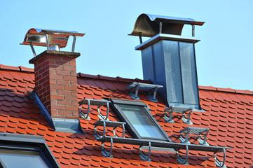 Schornsteine aus Ziegelmauerwerk und mit Blechverkleidung mit Edelstahlhaube sowie Dachtreppe und Dachfenstern auf einem Ziegeldach