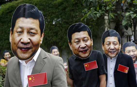 "Members of activist Party List group ""Akbayan"" don picture cut-out masks of Chinese President Xi Jinping as they pose outside a coffee shop in Quezon city"