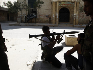 A Free Syrian Army fighter aims a RPG as he waits for Syrian Army tanks in the Salaheddine neighbourhood of central Aleppo