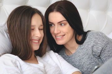 Beautiful mother and her cute teenage daughter looking something on smartphone, sitting in bedroom