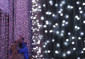 A couple takes a picture in front of a light installation for Christmas celebrations in Beijing