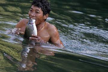 A Naga man carries fish in his teeth after it was stunned by dynamite in a creek between Donhe and Lahe township in the Naga Self-Administered Zone