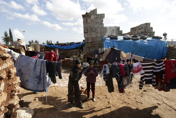 Children stand near hanging clothes outside ancient buildings, which displaced families are using as shelters, in the southern countryside of Idlib