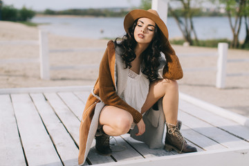 Beautiful model in hat and dress in hippie style posing on summer beach.