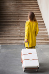 Young woman dressed in yellow suit holding suitcase and standing in front of stairs on railway station. View from the back.