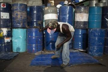 A man beats a sheet of metal cut from an oil barrel to use as recycling material in Kamukunji, Nairobi