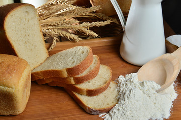Fresh bread and milk in jug on wooden board with wheat on background