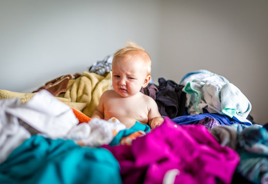 Cute Baby Disrupts Household Chores by Sitting in Pile of Clothes on Bed