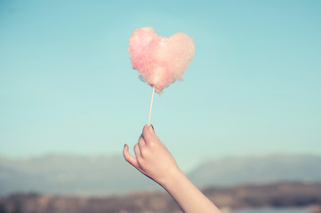 Pink cotton candy in a shape of a heart raised high over the hills to the light blue sky.