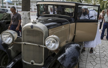 A man takes photograph of a vintage car displayed during an exhibition in Rouiba, on the outskirt of Algiers