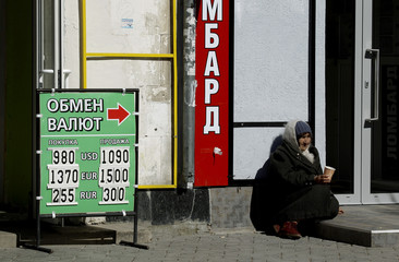 Woman begs for money outside a currency exchange office in central Simferopol