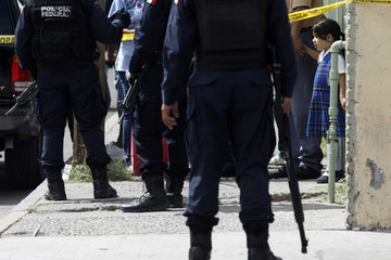 A girl leaves a school surrounded by police officers near a crime scene  where a man had been killed earlier in Ciudad Juarez