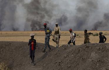 Rebel fighters walk in front of a bushfire in a rebel controlled territory in Upper Nile State