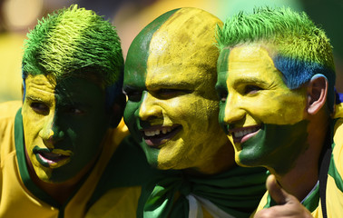 Brazilian fans pose for pictures while waiting for the start of the 2014 World Cup round of 16 game between Brazil and Chile at the Mineirao stadium in Belo Horizonte
