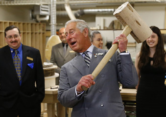 Britain's Prince Charles hefts a wooden mallet while touring a heritage retrofit carpentry exhibit at Holland College in Charlottetown