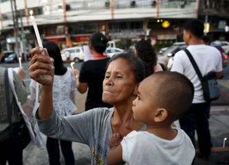 Woman carries her child as she joins a protest against Paris attacks, in Quezon city, metro Manila