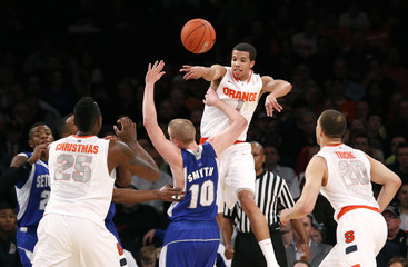 Syracuse Orange's Carter-Williams leaps and passes over Seton Hall Pirates' Smyth in the second half of their NCAA men's college basketball game in New York