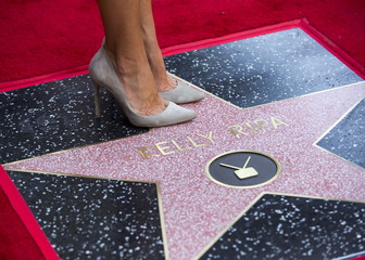 Television personality Ripa poses on her star after it was unveiled on the Hollywood Walk of Fame in Los Angeles