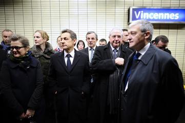 France's President Nicolas Sarkozy waits for a suburban train in Vincennes station near Paris