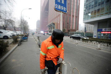 A cleaner walks along a street in Beijing's central business area