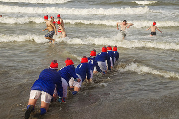 A group of girls crawl into the North Sea during the annual New Years Dive at Scheveningen