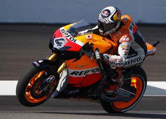 Honda MotoGP rider Andrea Dovizioso of Italy pops a wheelie coming out of a turn during practice prior to qualifications for the Indianapolis Grand Prix
