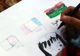 "A Libyan child colors a drawing featuring Qatari, French and the Kingdom of Libya flags and the word ""Leave"", at Court Square in Benghazi"
