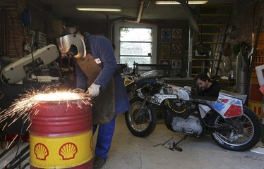 Vibrazioni's art design owner Alberto cuts an oil barrel as Riccardo works on a Harley Davidson motorbike personalised with parts of oil barrel, in Massa Lombarda