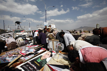 Anti-government protesters pray near bodies of fellow protesters and defected army soldiers during their funeral in Sanaa