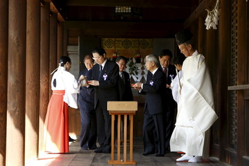 Japanese lawmakers receive sacred sake after they paid respects to the country's war dead at the Yasukuni shrine in Tokyo