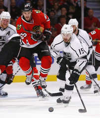 Blackhawks' Shaw jumps as Los Angeles Kings' Richardson reaches for the puck in the second period of Game 2 of their NHL Western Conference final hockey playoff game in Chicago