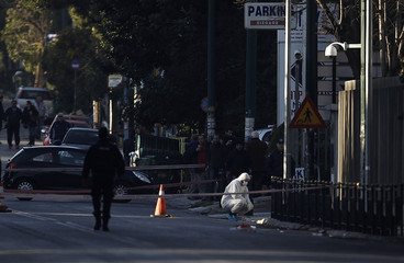 A police expert searches for evidence outside the German ambassador's residence in Chalandri suburb north of Athens