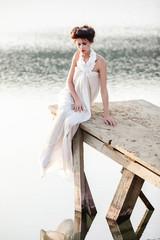 girl in white dresssitting on a wodden pier