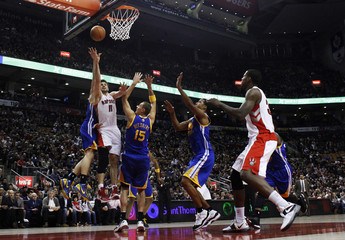 Raptors' Kleiza goes to the basket against Warriors' Biedrins during the first half of their NBA basketball game in Toronto