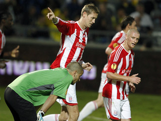 Stoke City's Crouch reacts after scoring a goal next to Maccabi Tel Aviv's Levy during their Europa League soccer match in Bloomfield Stadium in Tel Aviv