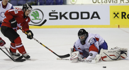 Norway's goalkeeper Haugen saves a puck ahead of Switzerland's Pluss during their qualification round Group F game in Kosice
