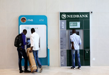 Customers queue to draw money from an ATM outside a branch of South Africa's Nedbank (R) and First National Bank (FNB)