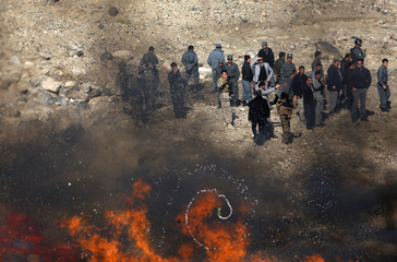 Afghan policemen stand behind a pile of burning narcotics in the outskirts of Kabul