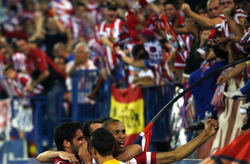 Atletico Madrid's Miranda celebrates a goal with his teammate Garcia during their Spanish first division soccer match against Elche at Vicente Calderon stadium in Madrid