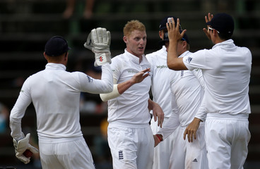 England cricket players celebrate the dismissal of South Africa's de Villiers after he was caught out by England's Stokes during the third cricket test match  in Johannesburg