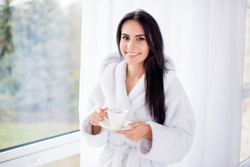 Nice beginning of day! Portrait of gorgeous brunette girl in bathrobe standing near window. She is smiling and holding a cup of coffee