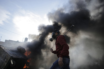 A Palestinian protester holds a slingshot near a burning tyre during clashes with Israeli troops, following the funeral of Palestinian minister Ziad Abu Ein near Ramallah