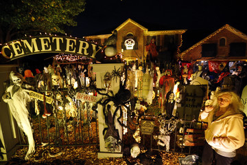 A visitor to a house covered in Halloween decorations looks over the scene in the front yard in the Chicago suburb of Naperville