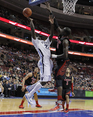 Villanova forward Pinkston shoots under pressure from Louisville center Deng during their NCAA basketball game in Philadelphia
