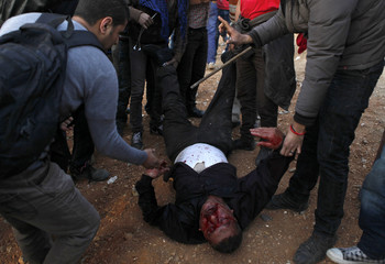 Anti-Mursi protesters beat a Muslim Brotherhood member during clashes near the Muslim Brotherhood's national headquarters in Cairo's Moqattam district