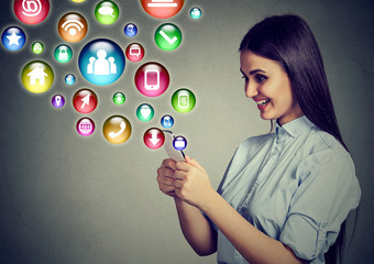 woman using smartphone with application icons flying out of screen