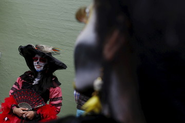 "Woman with her face painted to look like the popular Mexican figure called ""Catrina"", looks on as she takes part in the annual Catrina Fest in Mexico City"