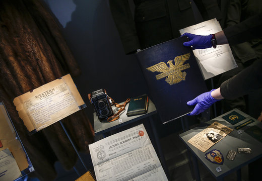 An assistants places the scrapbook belonging to war correspondent Virginia Irwin into a display at The American Air Museum