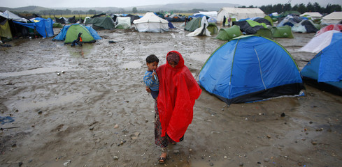 A refugee woman carrying her child walks under heavy rainfall at a makeshift camp for migrants and refugees at the Greek-Macedonian border near the village of Idomeni