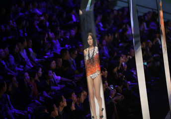A model is reflected in a mirror as she presents a creation by Aimer during Shanghai Fashion